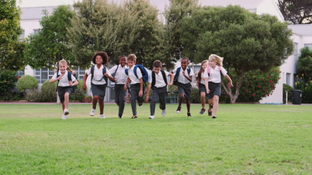 休憩時間にフィールドを横切って走る制服を着た興奮した小学生 - 制服点の映像素材/bロール
