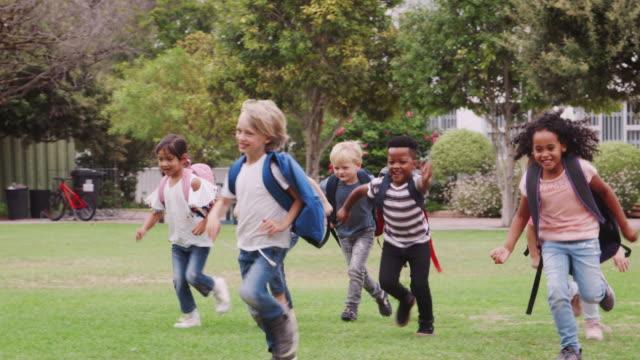 upphetsad grundskola elever bär uniform löper över fältet vid rasttid - mänsklig ålder bildbanksvideor och videomaterial från bakom kulisserna