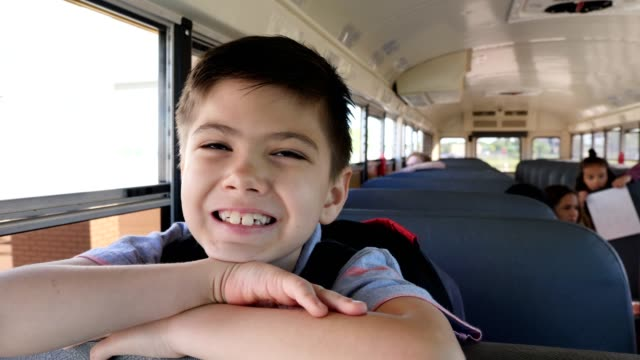 vídeos y material grabado en eventos de stock de estudiante de primaria excitado en el autobús escolar - autobuses escolares