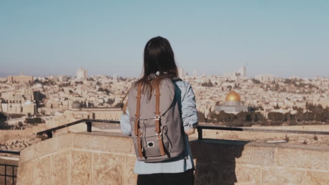 excited european tourist girl raises hands happy. israel, jerusalem. woman with arms wide open. freedom. slow motion - esploratore video stock e b–roll