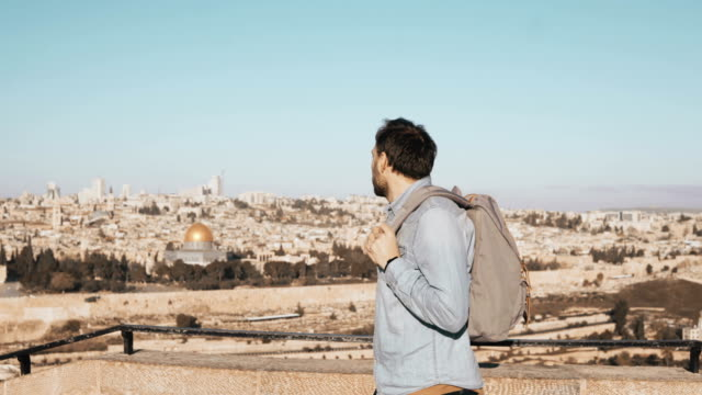 Excited European tourist male looks around. Israel, Jerusalem. Happy smiling man with backpack enjoys beautiful view 4K video