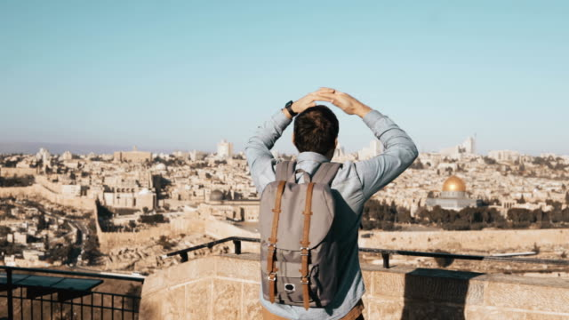 Excited European tourist male raises hands. Israel, Jerusalem. Arms wide open. Man with backpack enjoys amazing view 4K video