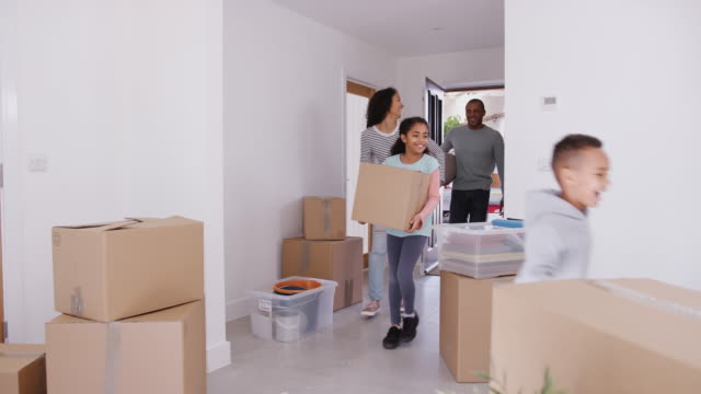 Excited family carrying boxes and rug into new home on moving in day - shot in slow motion video