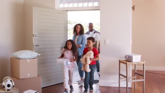 excited family carrying boxes into new home on moving day - new home stock videos & royalty-free footage
