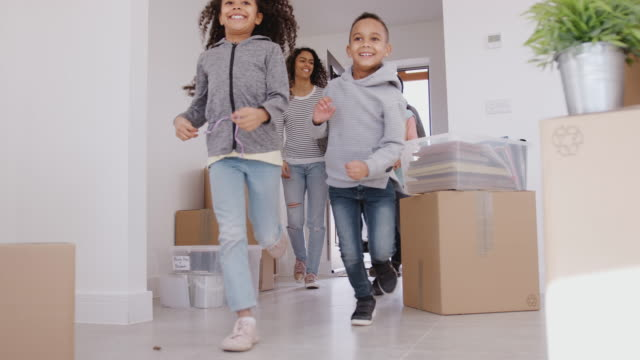Excited family carrying boxes into new home on moving in day - shot in slow motion Smiling Family Carrying Boxes Into New Home On Moving Day new home stock videos & royalty-free footage
