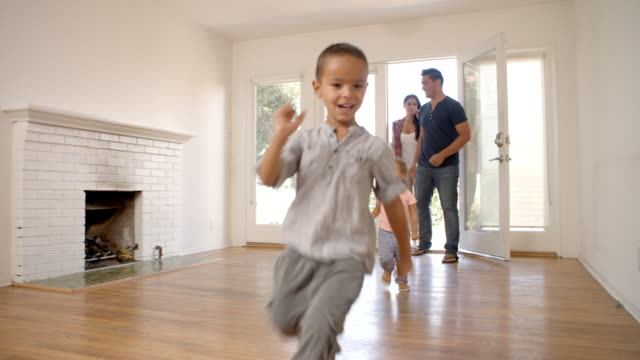 excited family explore new home on moving day - new home stock videos and b-roll footage