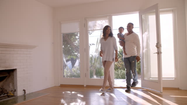 Excited Family Explore New Home On Moving Day