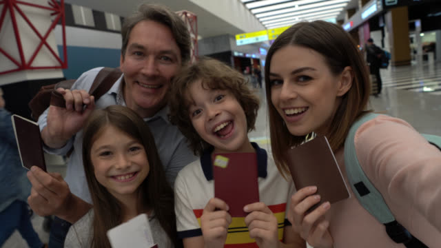 Excited family taking a selfie at the airport with their passports and boarding passes facing camera smiling