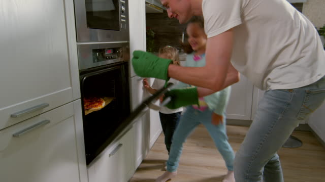Excited Family Taking Pizza out of Oven - vídeo