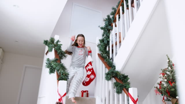 stockvideo's en b-roll-footage met enthousiast familie dragend pyjama's trap holding kousen op kerstochtend rennen - christmas tree