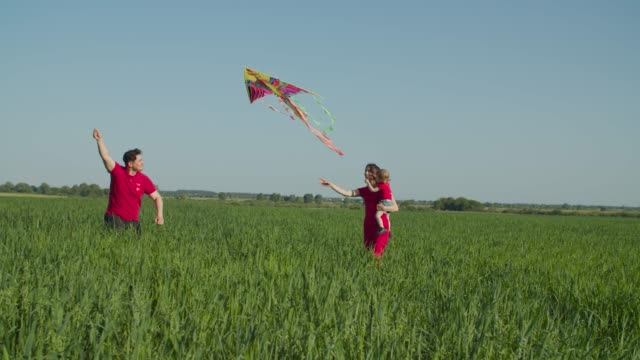 Excited family with little kid running with kite