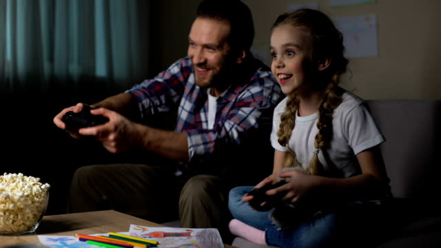 excited father and daughter pressing console buttons while playing video game - развлекательные игры стоковые видео и кадры b-roll