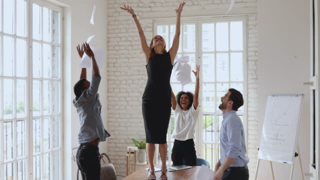 Excited female boss and team dancing throwing papers in office