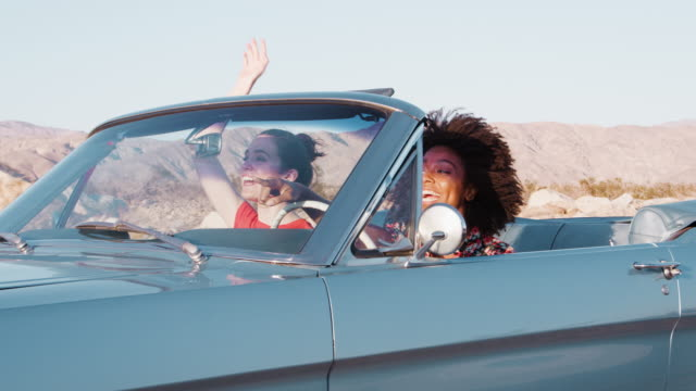 vídeos de stock e filmes b-roll de excited female friends driving convertible car on a highway - afro americano