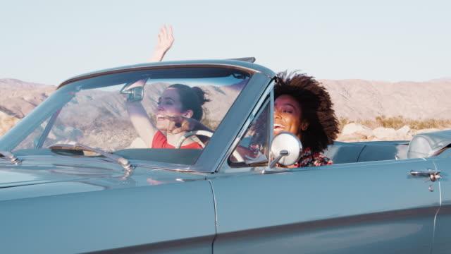 stockvideo's en b-roll-footage met opgewonden vriendinnen converteerbare auto rijden op een snelweg - afro amerikaanse etniciteit