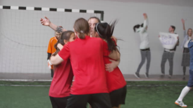 Excited Female Soccer Team Celebrating Goal on Field Group of young joyous female players jumping, huddling and giving high five to each other while celebrating soccer goal during match on indoor sports field huddling stock videos & royalty-free footage