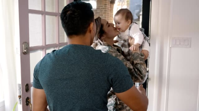excited female soldier is warmly greeted by family - moglie video stock e b–roll
