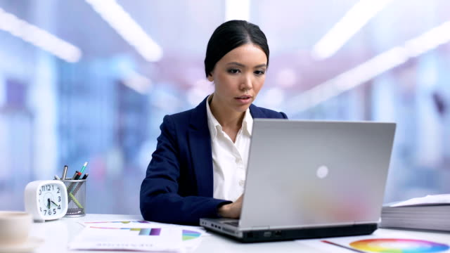 Excited female worker reading email showing yes gesture, successful agreement Excited female worker reading email showing yes gesture, successful agreement representing stock videos & royalty-free footage