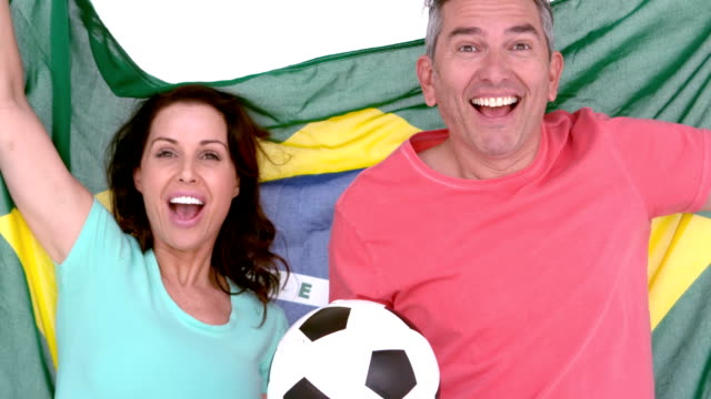 Excited football fan couple holding brazil flag video