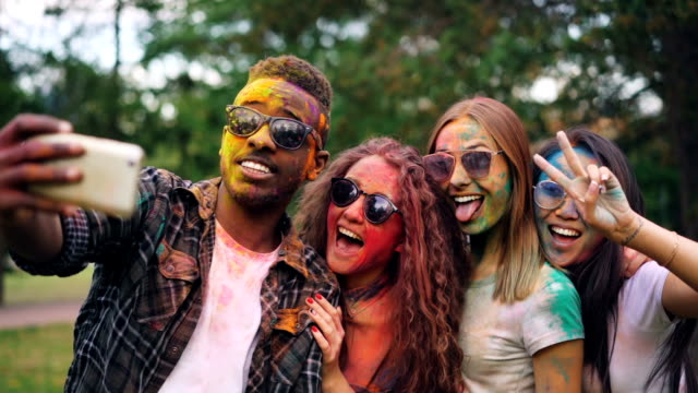 vídeos de stock e filmes b-roll de excited friends girls and guys are taking selfie with colored faces and hair using smartphone, stylish young man is jumping and laughing. modern technology and party concept. - descuidado