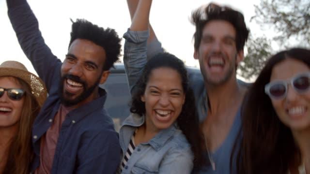 Excited friends on a road trip cheering beside camper van video