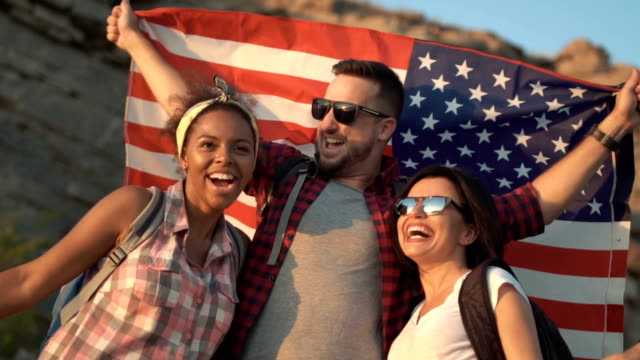 Excited friends posing among rocks with flag video