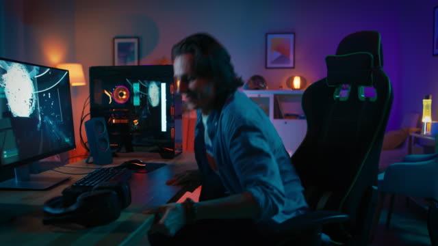 aufgeregt kommt an den tisch, setzt auf seine kopfhörer mit mikrofon und startet die wiedergabe von online-video-spiel auf seinem pc gamer. zimmer und pc haben bunte neonlichter geführt. gemütlichen sie abend zu hause. - computerspieler stock-videos und b-roll-filmmaterial