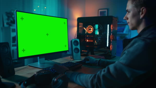 Excited Gamer Playing Online Video Game with a Mock Up Green Screen on His Powerful Personal Computer. Room and PC have Colorful Neon Led Lights. Cozy Evening at Home.