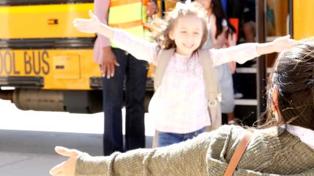 excited girl greets her mom with a hug after school - bus driver stock videos and b-roll footage