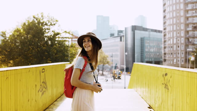 excited girl in hat, long hair walks on a bridge. european female traveller happy, turn round between yellow walls. 4k - rotterdam video stock e b–roll