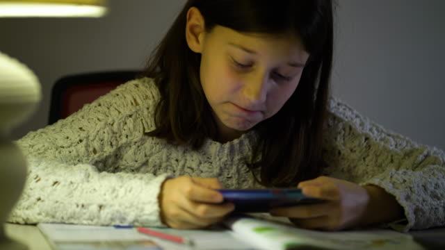 heyecanlı kız akşam evde akıllı telefon kullanarak online oyun oynuyor - dijital yerli stok videoları ve detay görüntü çekimi