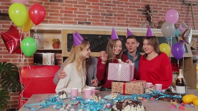 興奮した女の子、誠実な友人に囲まれて誕生日を開くプレゼント、お客様の笑顔の中で大きなソファに座って若い美しいブルネット - プレセントの箱点の映像素材/bロール