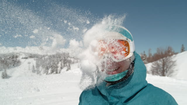 slowmotion: glada flicka klädd skidglasögon får slog i huvudet av snöboll. - snow kids bildbanksvideor och videomaterial från bakom kulisserna