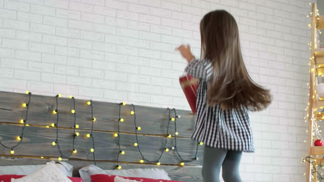 excited girl with christmas present - ricevere video stock e b–roll