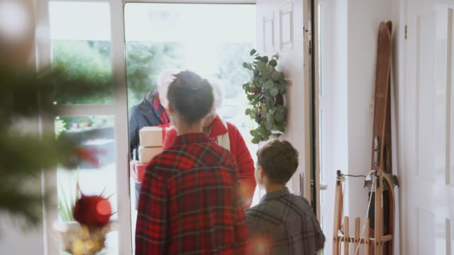 stockvideo's en b-roll-footage met opgewonden kleinkinderen groet grootouders met presenteert bezoeken op kerstdag - christmas family