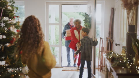 Excited Grandchildren Greeting Grandparents With Presents Visiting On Christmas Day Excited children greeting grandparents at front door as they arrive with presents to celebrate multi-generation family Christmas - shot in slow motion christmas stock videos & royalty-free footage