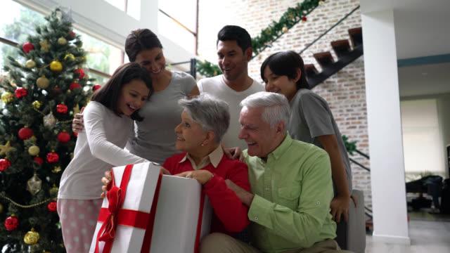 upphetsad mormor öppnar en stor julklapp medan kärleksfull familj är runt hennes leende - christmas present bildbanksvideor och videomaterial från bakom kulisserna