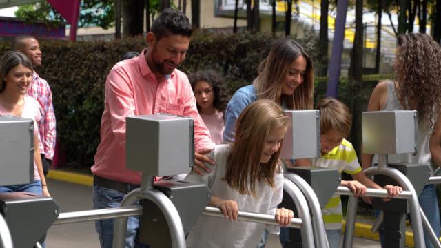 upphetsad grupp människor in en temapark som passerar genom vändkorsen - fritidsanläggning bildbanksvideor och videomaterial från bakom kulisserna