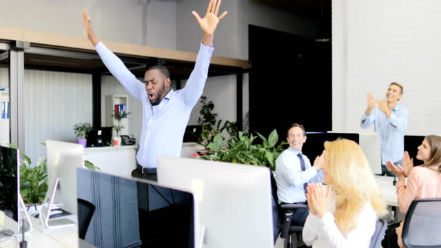 excited happy businessman celebrating success with team of business people clapping hands in modern office, african american man winner - достижение стоковые видео и кадры b-roll