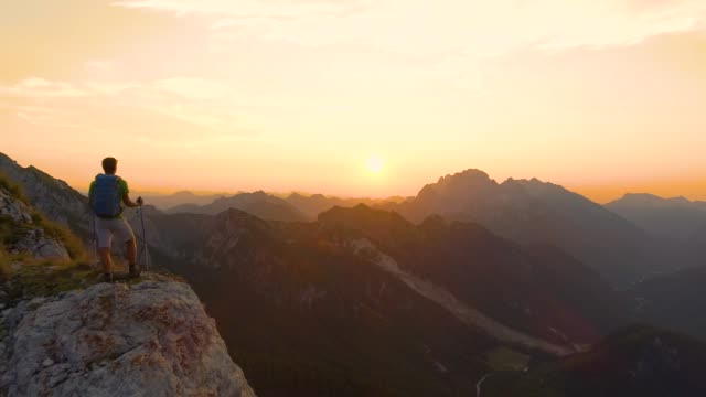 AERIAL: Excited hiker outstretches arms as he watches the sunset from a cliff.