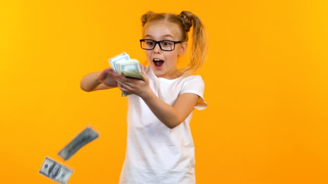 Excited kid throwing money, celebrating victory at talent show, jack-pot winner