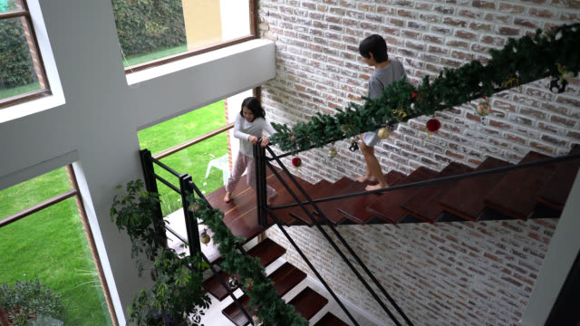stockvideo's en b-roll-footage met opgewonden kinderen lopen de trap op kerst ochtend naar de woonkamer waar ouders en grootouders op hen wachten - christmas tree