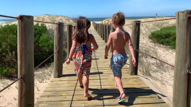 Excited kids running towards beach on wooden pathway