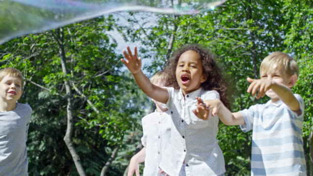 Excited Little Children Popping Huge Soap Bubble Excited blonde boys and little African girl popping giant soap bubble in the air while playing outdoors giant fictional character stock videos & royalty-free footage