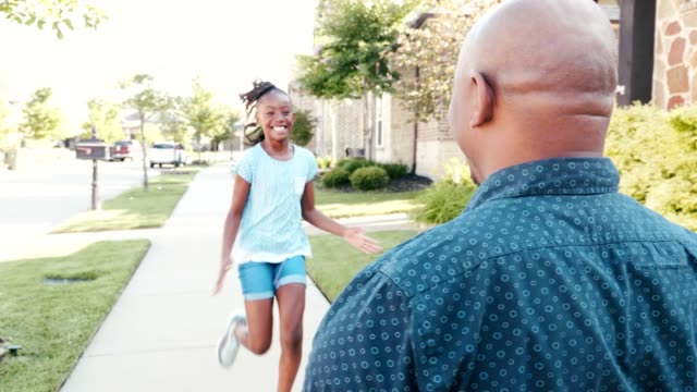 Excited little girl greets her dad