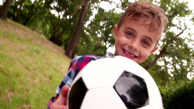 felice piccolo con il calcio in piedi e sorride - solo un bambino maschio video stock e b–roll