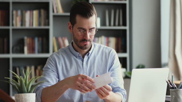 Excited male worker entrepreneur opening mail letter reading good news Excited male worker entrepreneur opening mail letter reading good news celebrating success. Happy businessman receiving loan approval, salary bonus, get promoted concept sitting at home office desk goal post stock videos & royalty-free footage