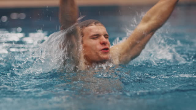 vídeos de stock e filmes b-roll de excited man cheering after diving into water - swim arms