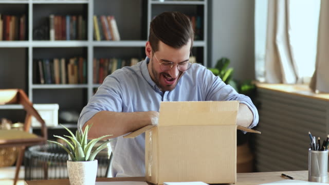 Excited man customer opening cardboard parcel box receiving gift
