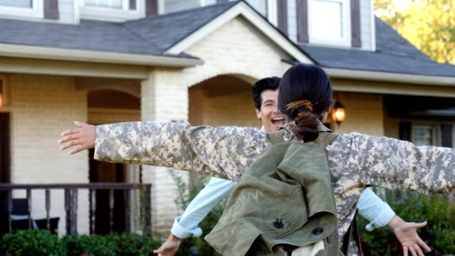 Excited man greets wife after long military deployment Excited mid adult Hispanic man runs to greet his returning wife from long overseas military deployment. The female soldier welcomes him with outstretched arms. The man picks up the woman as they spin around. veteran stock videos & royalty-free footage